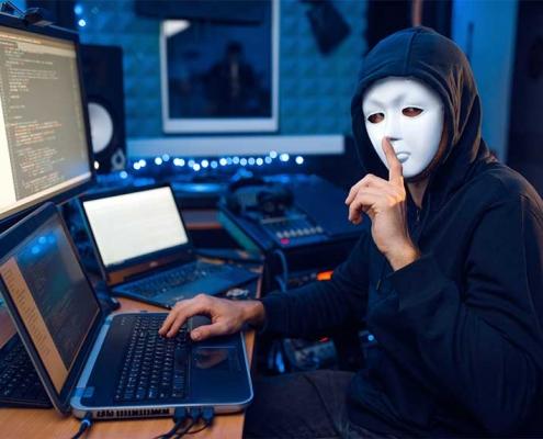 Un hacker avec masque devant des ordinateurs