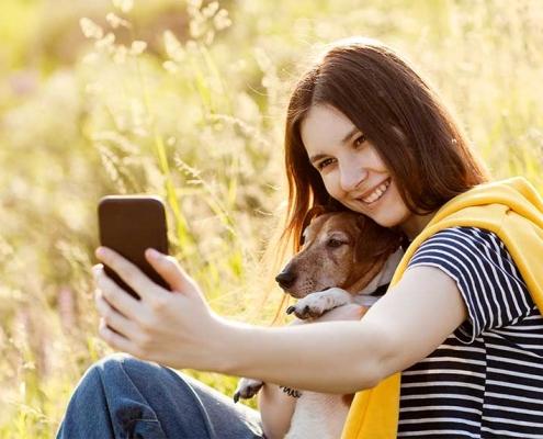 Belle fille avec chien prends un selfie